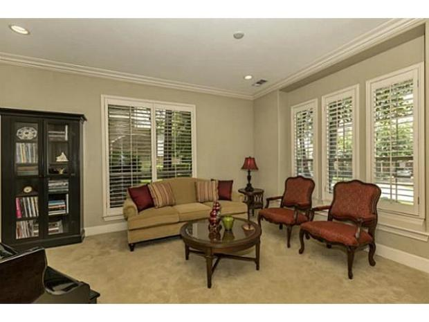 Large windows in formal living area with plantation shutters.