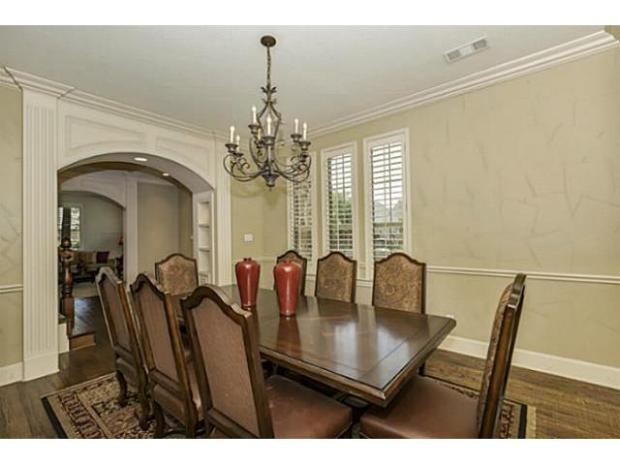 Formal dining room with crown molding and gorgeous archway.