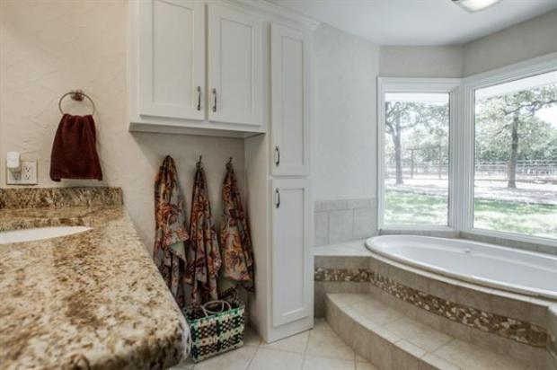 Master bath  featuring granite counters, garden tub, and separat
